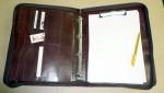 Zipová spisovka kožená s kroužkovou vazbou, vnitřními i jednou vnější kapsou a klipsem na doklady v pravé vnitřní části.